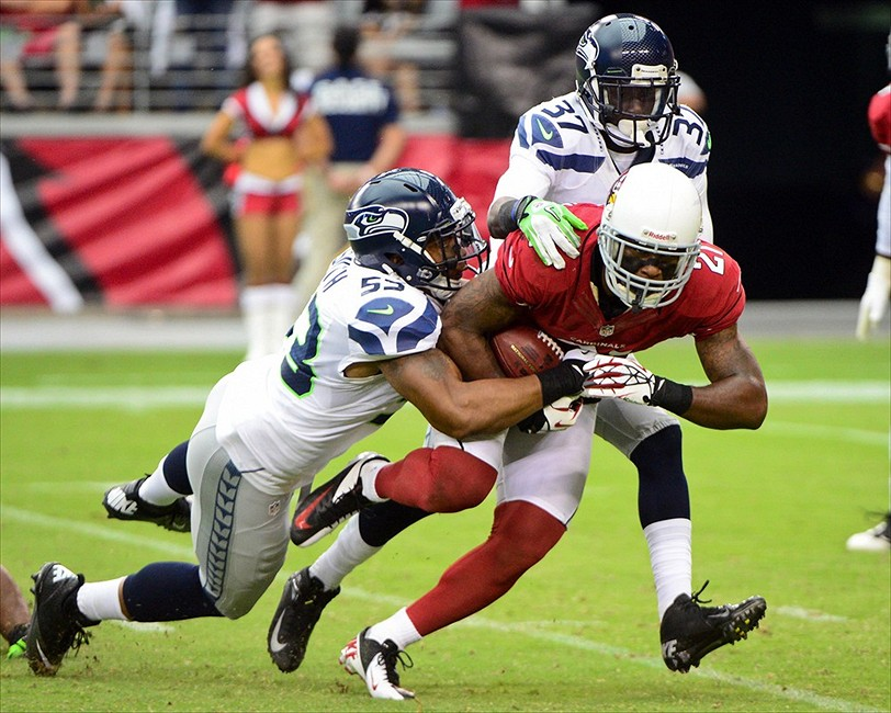 Sept. 9, 2012; Glendale, AZ, USA; Arizona Cardinals cornerback Patrick Peterson (21) is tackled by Seattle Seahawks linebacker Malcolm Smith (53) and cornerback Jeremy Lane (37) during the second half at University of Phoenix Stadium. The Cardinals beat the Seahawks 20-16. Mandatory Credit: Matt Kartozian-USA TODAY Sports