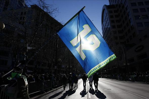 Feb 5, 2014; Seattle, WA, USA; A Seattle Seahawks fan carries a 12th Man flag down 4th Avenue before a Super Bowl championship parade to begin in downtown Seattle. Mandatory Credit: Joe Nicholson-USA TODAY Sports