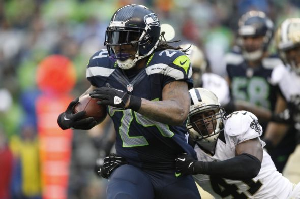 Jan 11, 2014; Seattle, WA, USA; Seattle Seahawks running back Marshawn Lynch (24) runs the football against New Orleans Saints strong safety Roman Harper (41) during the second half of the 2013 NFC divisional playoff football game at CenturyLink Field. Mandatory Credit: Joe Nicholson-USA TODAY Sports