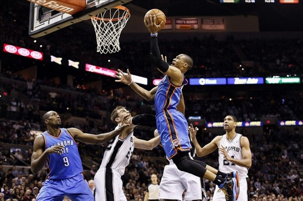 Mar 11, 2013; San Antonio, TX, USA; Oklahoma City Thunder guard Russell Westbrook (0) drives to the basket as San Antonio Spurs forward Tiago Splitter (left) looks on during the second half at the AT