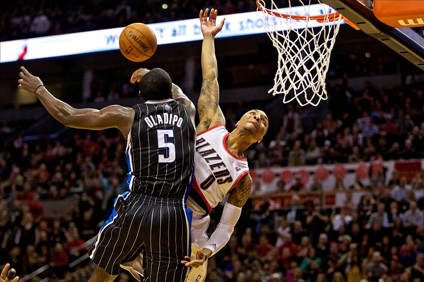 Jan 8, 2014; Portland, OR, USA; Portland Trail Blazers point guard Damian Lillard (0) has a dunk attempt blocked by Orlando Magic shooting guard Victor Oladipo (5) at the Moda Center. Mandatory Credit: Craig Mitchelldyer-USA TODAY Sports
