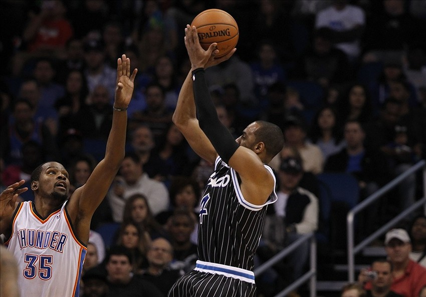Feb 7, 2014; Orlando, FL, USA; Orlando Magic shooting guard Arron Afflalo (4) shoots the ball over Oklahoma City Thunder small forward Kevin Durant (35) defends during the first half at Amway Center. Mandatory Credit: Kim Klement-USA TODAY Sports
