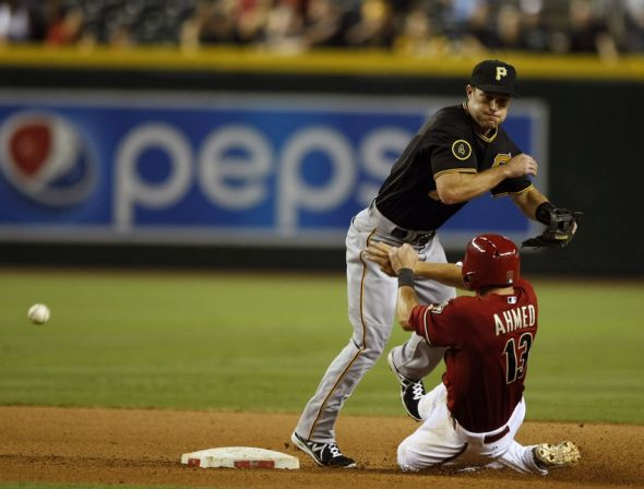 Aug 3, 2014; Phoenix, AZ, USA; Arizona Diamondbacks shortstop Nick Ahmed (13) blocks the throw of Pittsburgh Pirates second baseman Jayson Nix (27) while turning a double play in the tenth inning allowing the game winning run to score at Chase Field. The Diamondbacks defeated the Pirates 3-2. Mandatory Credit: Rick Scuteri-USA TODAY Sports
