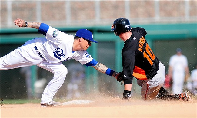 Mar. 6, 2012; Phoenix, AZ, USA; Los Angeles Dodgers infielder Justin Sellers (left) tags out San Francisco Giants baserunner Gary Brown (10) during the eighth inning during a spring training game against San Francisco Giants at Camelback Ranch. Mandatory Credit: Jennifer Hilderbrand-US PRESSWIRE