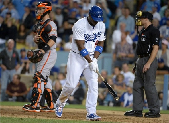 Sep 13, 2013; Los Angeles, CA, USA; Los Angeles Dodgers right fielder Yasiel Puig (66) reacts after striking out in the ninth inning as San Francisco Giants catcher Buster Posey (left) and home plate umpire Dan Iassogna (right) watch at Dodger Stadium. The Giants defeated the Dodgers 4-2. Mandatory Credit: Kirby Lee-USA TODAY Sports