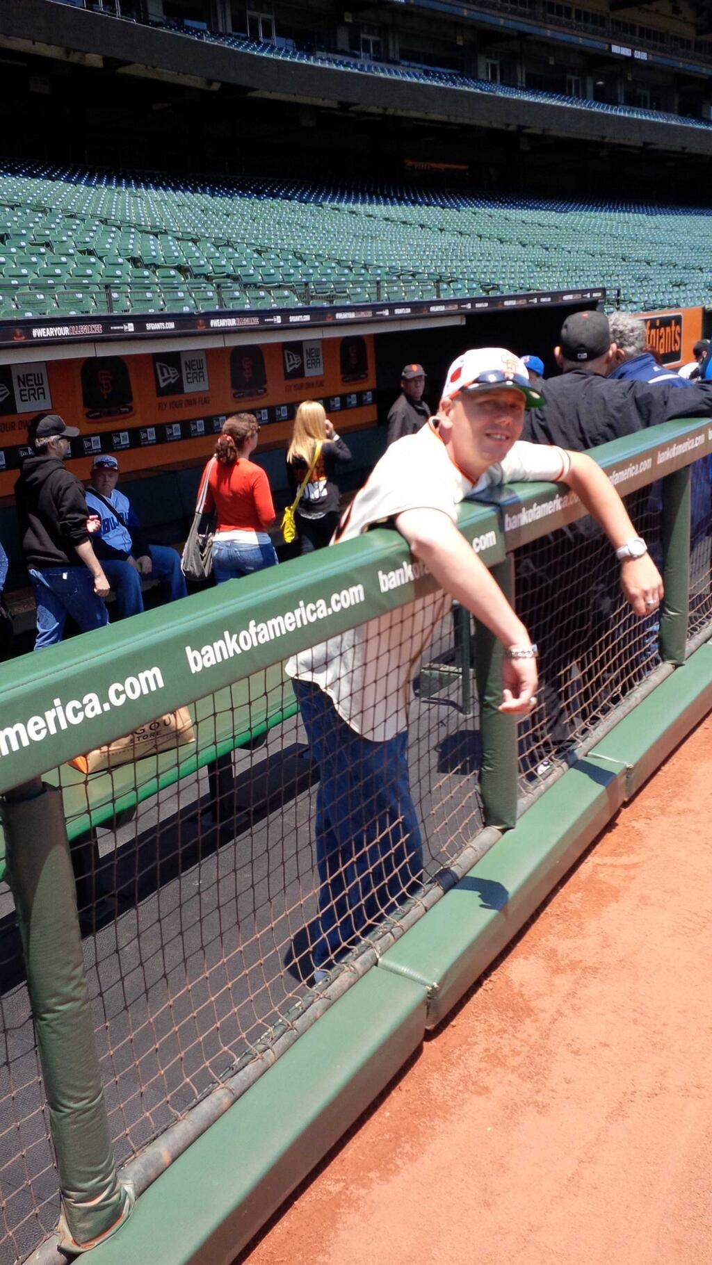 Leaning on the Dugout railing.