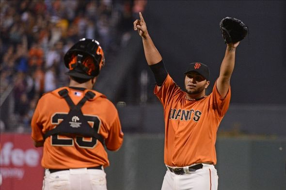 Yusmeiro Petit of the San Francisco Giants, raises his arms in victory.