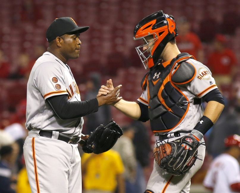 May 2, 2016; Cincinnati, OH, USA; San Francisco Giants relief pitcher Santiago Casilla (left) is congratulated by catcher Buster Posey (right) after the Giants defeated the Cincinnati Reds 9-6 at Great American Ball Park. Mandatory Credit: David Kohl-USA TODAY Sports