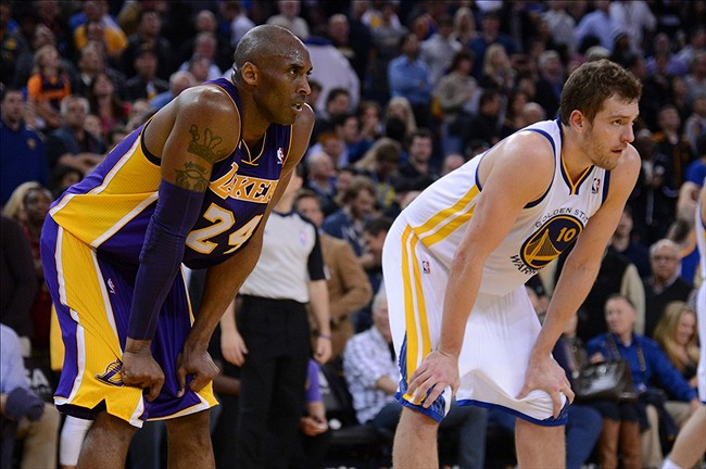 March 25, 2013; Oakland, CA, USA; Los Angeles Lakers shooting guard Kobe Bryant (24) rests next to Golden State Warriors power forward David Lee (10) during the fourth quarter at Oracle Arena. The Warriors defeated the Lakers 109-103. Mandatory Credit: Kyle Terada-USA TODAY Sports
