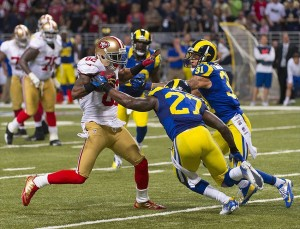 Dec 2, 2012; St. Louis, MO, USA; San Francisco 49ers wide receiver Mario Manningham (82) attempts to break away from St. Louis Rams free safety Quintin Mikell (27) and Rams cornerback Cortland Finnegan (31) during the second half at the Edward Jones Dome. The Rams defeated the 49ers 16-13 in overtime. Mandatory Credit: Photo by Scott Rovak-USA TODAY Sports
