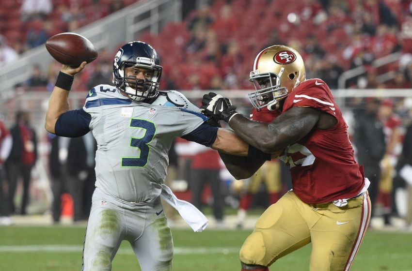 November 27, 2014; Santa Clara, CA, USA; Seattle Seahawks quarterback Russell Wilson (3) passes the football against San Francisco 49ers defensive end Tank Carradine (95) during the fourth quarter at Levi's Stadium. The Seahawks defeated the 49ers 19-3. Mandatory Credit: Kyle Terada-USA TODAY Sports