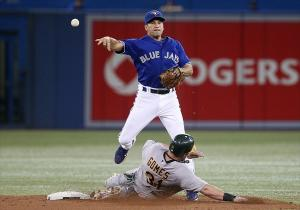 Jul 26, 2012; Toronto, ON, Canada; Toronto Blue Jays shortstop Omar Vizquel (17) gets the force out at second base in the 5th inning as Oakland Athletics right fielder Johnny Gomes (31) slides at the Rogers Centre. Mandatory Credit: Tom Szczerbowski-USA TODAY Sports