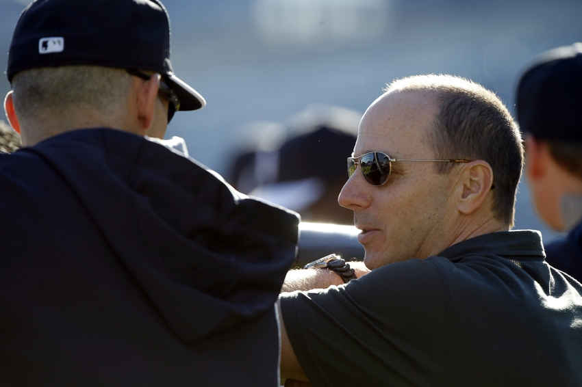 Feb 18, 2014; Tampa, FL, USA; New York Yankees general manager Brian Cashman and manager Joe Girardi (28) talk as they watch batting practice at Steinbrenner Field. Mandatory Credit: Kim Klement-USA TODAY Sports