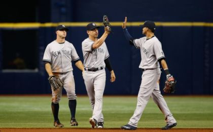 Sep 21, 2016; St. Petersburg, FL, USA; New York Yankees left fielder Brett Gardner (11), center fielder Jacoby Ellsbury (22) and center fielder Mason Williams (66) congratulate each other as they beat the Tampa Bay Rays at Tropicana Field. New York Yankees defeated the Tampa Bay Rays 11-5. Mandatory Credit: Kim Klement-USA TODAY Sports