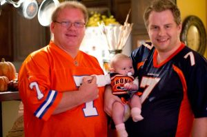 Tyler, despite growing up in Kansas, is a die hard Bronco fan. Tyler is shown with his dad, Chuck, and his daughter Domenico. Very nice attire!