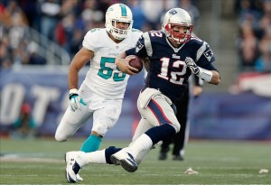 Oct 27, 2013; Foxborough, MA, USA; New England Patriots quarterback Tom Brady (12) runs for a first down past Miami Dolphins outside linebacker Koa Misi (55)during the fourth quarter of their 27-17 win at Gillette Stadium. Mandatory Credit: Winslow Townson-USA TODAY Sports
