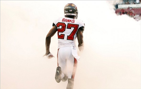 Aug 29, 2013; Tampa, FL, USA; Tampa Bay Buccaneers cornerback Johnthan Banks (27) is announced as he runs through the smoke prior to the game against the Washington Redskins at Raymond James Stadium. Mandatory Credit: Kim Klement-USA TODAY Sports