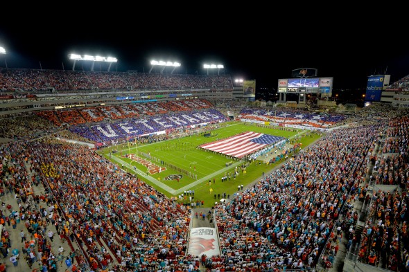 An overall inside view of Raymond James Stadium as fans honor military and veterans before a NFL game between the Miami Dolphins and Tampa Bay Buccaneers, Monday, November 11, 2013 in Tampa, Fla. 50,000 cards were provided to fans by USAA, the official military appreciation sponsor of the NFL. (Scott Miller/AP Images for USAA)