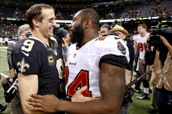 Dec 29, 2013; New Orleans, LA, USA; New Orleans Saints quarterback Drew Brees (9) talks with Tampa Bay Buccaneers cornerback Darrelle Revis (24) following a win in a game at the Mercedes-Benz Superdome.The Saints defeated the Buccaneers 42-17. Mandatory Credit: Derick E. Hingle-USA TODAY Sports
