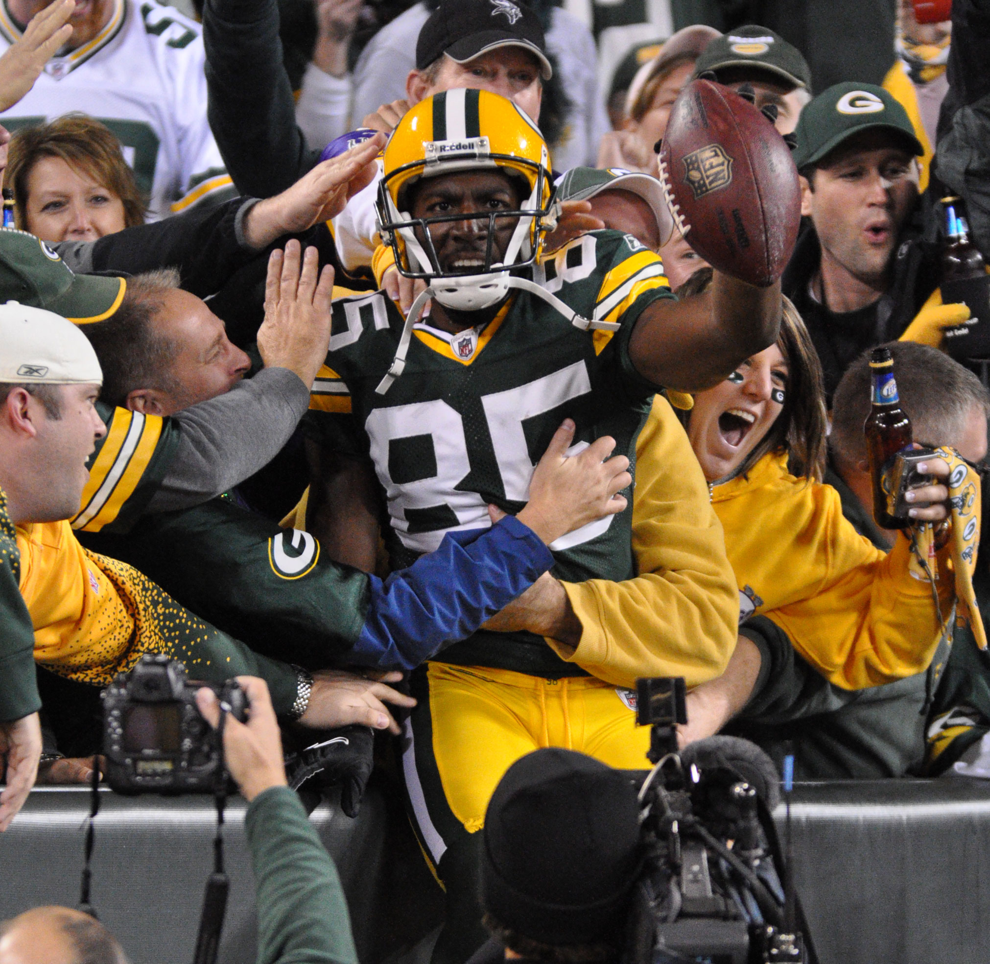 Greg Jennings celebrates a Lambeau Leap with fans after one of his 55 touchdowns he scored with the Packers. Raymond T. Rivard photograph