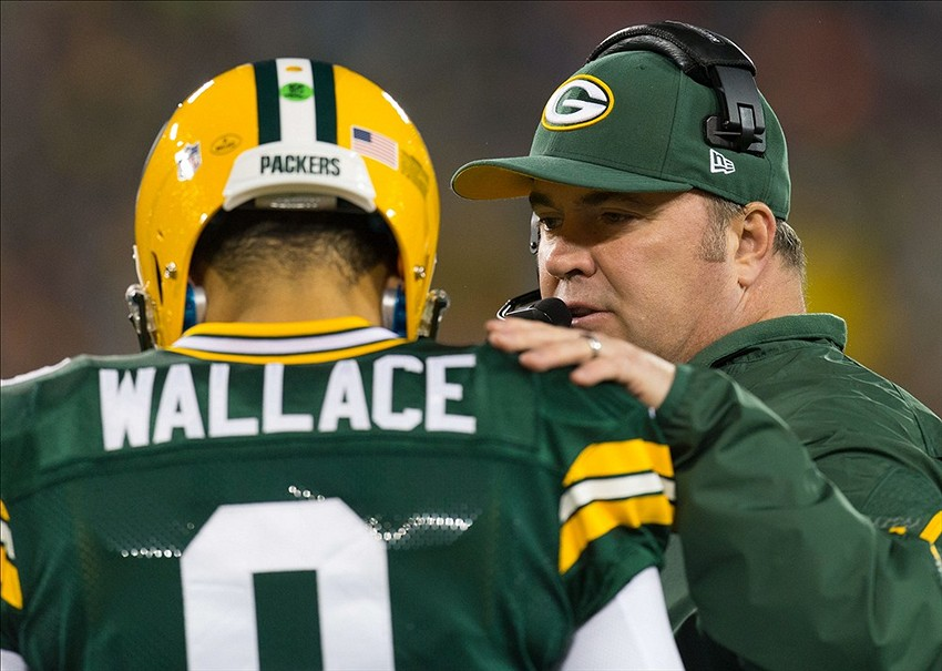 Nov 4, 2013; Green Bay, WI, USA; Green Bay Packers head coach Mike McCarthy talks with quarterback Seneca Wallace (9) during the first quarter against the Chicago Bears at Lambeau Field. Mandatory Credit: Jeff Hanisch-USA TODAY Sports