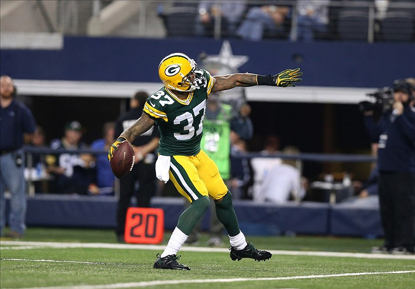 Sam Shields (37) throws the ball into the stands after an interception in the fourth quarter against Dallas Cowboys receiver Miles Austin (19) at AT&T stadium.