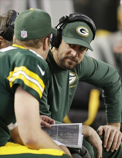 Aaron Rodgers talks with quarterback Matt Flynn on the bench during Sunday's game against the Dallas Cowboys.
