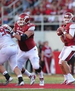 Arkansas Razorbacks quarterback Tyler Wilson (8) looks to pass as center Travis Swanson (64) block against the Jacksonville State Gamecocks. Nelson Chenault-USA TODAY Sports