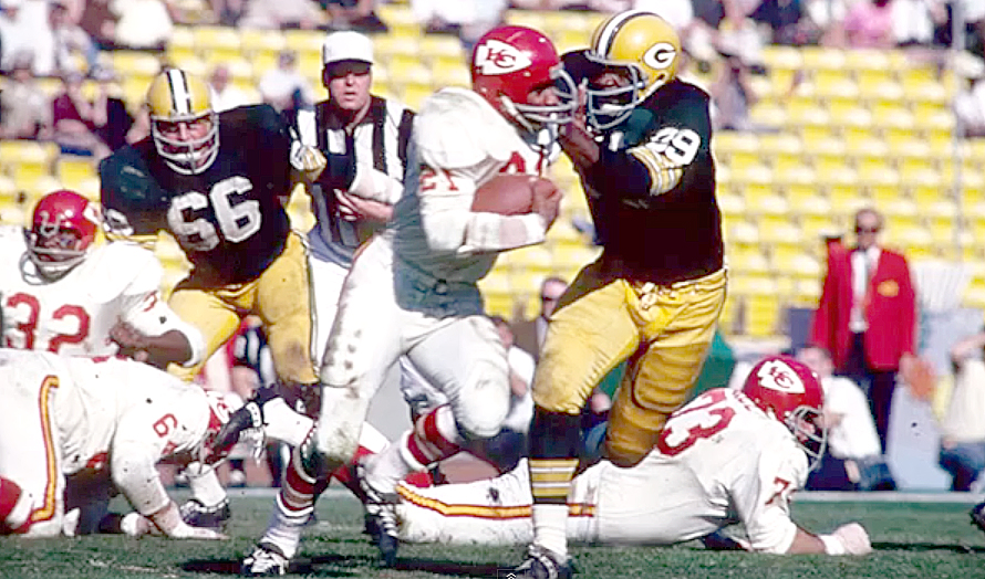 Kansas City Chiefs running back Mike Garrett is tackled by Green Bay Packers linebacker Dave Robinson, while Packers middle linebacker Ray Nitschke watches during Super Bowl I action.