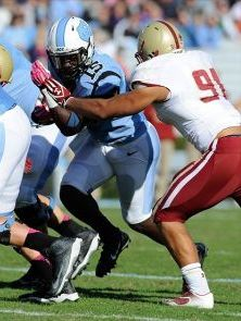 North Carolina Tar Heels tailback A.J. Blue (15) drives past Boston College Eagles defensive end Kasim Edebali (91). Liz Condo-USA TODAY Sports
