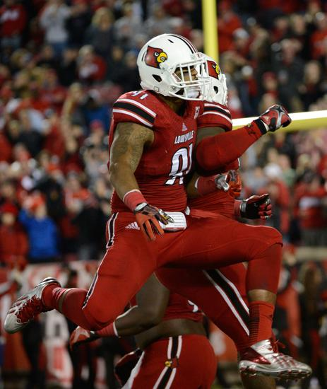 Nov 16, 2013; Louisville, KY, USA; Louisville Cardinals defensive end Marcus Smith (91) and defensive tackle Roy Philon (93) celebrate after a defensive stop during the second half of play against the Houston Cougars at Papa John