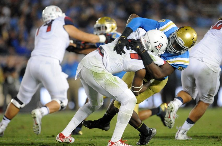 UCLA Bruins defensive lineman Takkarist McKinley (98) brings down Arizona Wildcats quarterback Khalil Tate (14) during the second half at Rose Bowl. Gary A. Vasquez-USA TODAY Sports