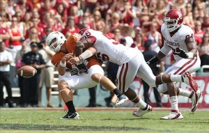 Oct 8, 2011; Dallas, TX, USA; Texas Longhorns quarterback David Ash (14) fumbles in the third quarter from a tackle by Oklahoma Sooners defensive end Ronnell Lewis (56) for the red river rivalry at the Cotton Bowl. Mandatory Credit: Matthew Emmons-US PRESSWIRE