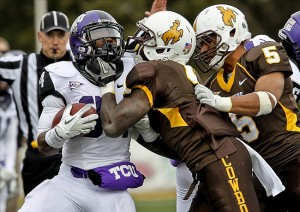 Nov 5, 2011; Laramie, WY, USA; TCU Horned Frogs running back Ed Wesley (34) is tackled by Wyoming Cowboys cornerback Tashaun Gipson (4) and linebacker Korey Jones (5) in the second quarter at War Memorial Stadium. Mandatory Credit: Troy Babbitt-US PRESSWIRE