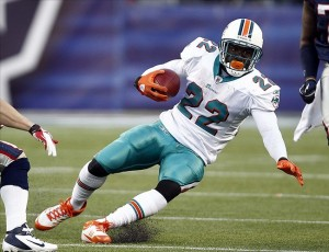Dec 24, 2011; Foxborough, MA, USA; Miami Dolphins running back Reggie Bush (22) carries the ball against the New England Patriots during the second half at Gillette Stadium. Mandatory Credit: Mark L. Baer-US PRESSWIRE