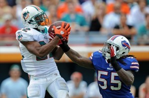 Nov 20, 2011; Miami, FL, USA; Miami Dolphins running back Reggie Bush (22) hauls in a catch as Buffalo Bills inside linebacker Kelvin Sheppard (55) defends during the first half at Sun Life Stadium. Mandatory Credit: Steve Mitchell-USA TODAY Sports