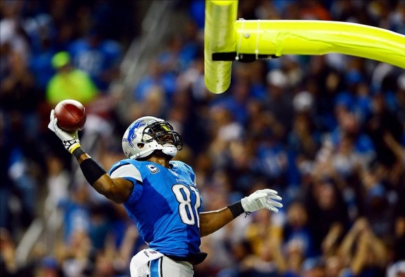 Nov 28, 2013; Detroit, MI, USA; Detroit Lions wide receiver Calvin Johnson (81) dunks the football over the goal post after scoring a touchdown during the third quarter of a NFL football game against the Green Bay Packers on Thanksgiving at Ford Field. Mandatory Credit: Andrew Weber-USA TODAY Sports