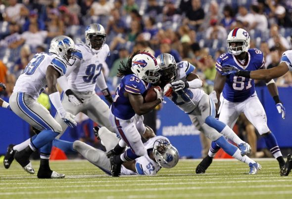 Aug 29, 2013; Orchard Park, NY, USA; Buffalo Bills running back Zach Brown (35) is tackled by Detroit Lions cornerback Bill Bentley (28) during the second half at Ralph Wilson Stadium. Mandatory Credit: Kevin Hoffman-USA TODAY Sports