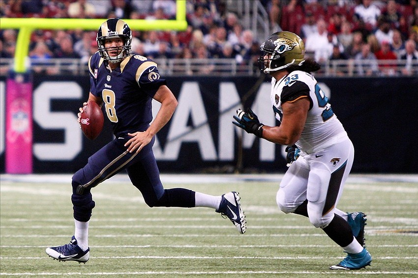 Oct 6, 2013; St. Louis, MO, USA; St. Louis Rams quarterback Sam Bradford (8) scrambles with the ball while while under pressure from Jacksonville Jaguars defensive end Tyson Alualu (93) at The Edward Jones Dome. Mandatory Credit: Scott Kane-USA TODAY Sports