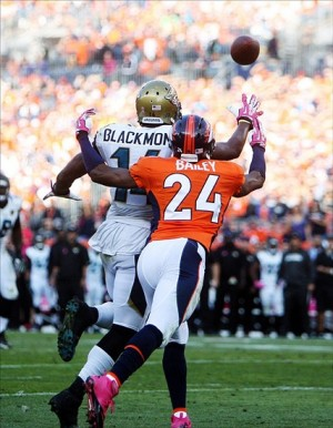 Oct 13, 2013; Denver, CO, USA; Jacksonville Jaguars wide receiver Justin Blackmon (14) attempts to catch a pass while being covered by Denver Broncos cornerback Champ Bailey (24) during the second half at Sports Authority Field at Mile High. The Broncos won 35-19. Mandatory Credit: Chris Humphreys-USA TODAY Sports