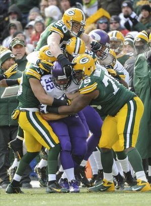 Nov 24, 2013; Green Bay, WI, USA; Minnesota Vikings running back Toby Gerhart (32) is tackled by Green Bay Packers linebacker A.J. Hawk (50) and defensive end Mike Daniels (76) in the 1st quarter at Lambeau Field. The Packers and Vikings finished in a tie 26-26. Mandatory Credit: Benny Sieu-USA TODAY Sports