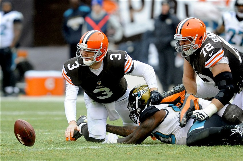Dec 1, 2013; Cleveland, OH, USA; Cleveland Browns quarterback Brandon Weeden (3) watches as the ball gets away after being stripped by Jacksonville Jaguars defensive end Jason Babin (58) during the second quarter at FirstEnergy Stadium. Mandatory Credit: Ken Blaze-USA TODAY Sports