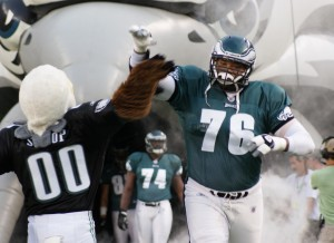 Eagles guard Stacy Andrews high fives Swoop.