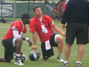Eagles quarterbacks Kevin Kolb and Mike Vick talk to offensive coordinator Marty Mornhinweg during practice.