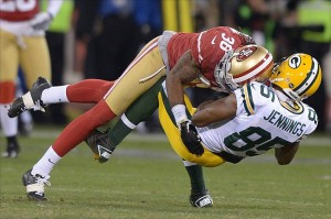 Jan 12, 2013; San Francisco, CA, USA; San Francisco 49ers safety Dashon Goldson (38) tackles Green Bay Packers receiver Greg Jennings (85) during the third quarter of the NFC divisional round playoff game at Candlestick Park. Mandatory Credit: Kirby Lee-USA TODAY Sports