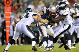 Aug 9, 2013; Philadelphia, PA, USA; New England Patriots quarterback Tim Tebow (5) is sacked by Philadelphia Eagles outside linebacker Jake Knott (54) and defensive end Vinny Curry (75) during the first half of a preseason game at Lincoln Financial Field. Mandatory Credit: Joe Camporeale-USA TODAY Sports