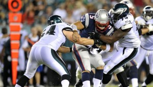 Vinny Curry, right, sacks Patriots quarterback Tim Tebow.