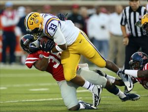 Oct 19, 2013; Oxford, MS, USA; LSU Tigers running back Jeremy Hill (33) advances the ball and is tackled by Mississippi Rebels linebacker Mike Marry (38) during the game at Vaught-Hemingway Stadium. Mandatory Credit: Spruce Derden-USA TODAY Sports
