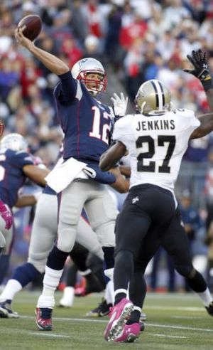 Oct 13, 2013; Foxborough, MA, USA; New England Patriots quarterback Tom Brady (12) throws a pass while being pressured by New Orleans Saints safety Malcolm Jenkins (27) during the second quarter at Gillette Stadium. Mandatory Credit: Stew Milne-USA TODAY Sports