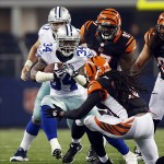 Aug 24, 2013; Arlington, TX, USA; Dallas Cowboys running back Phillip Tanner (34) runs the ball in the second quarter of the game against the Cincinnati Bengals free safety Reggie Nelson (20) at AT